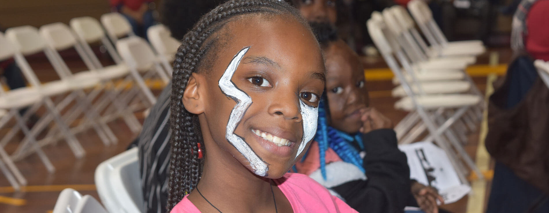 A child smiling while showing off her face paint.