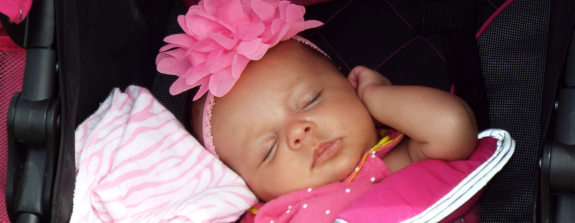 A sleeping baby in her car seat. She is snuggling a pink blanket and is wearing a pink hair band.