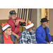 Four senior male residents, two wearing santa hats