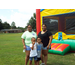 two adults with two children standing in front of a bouncy house